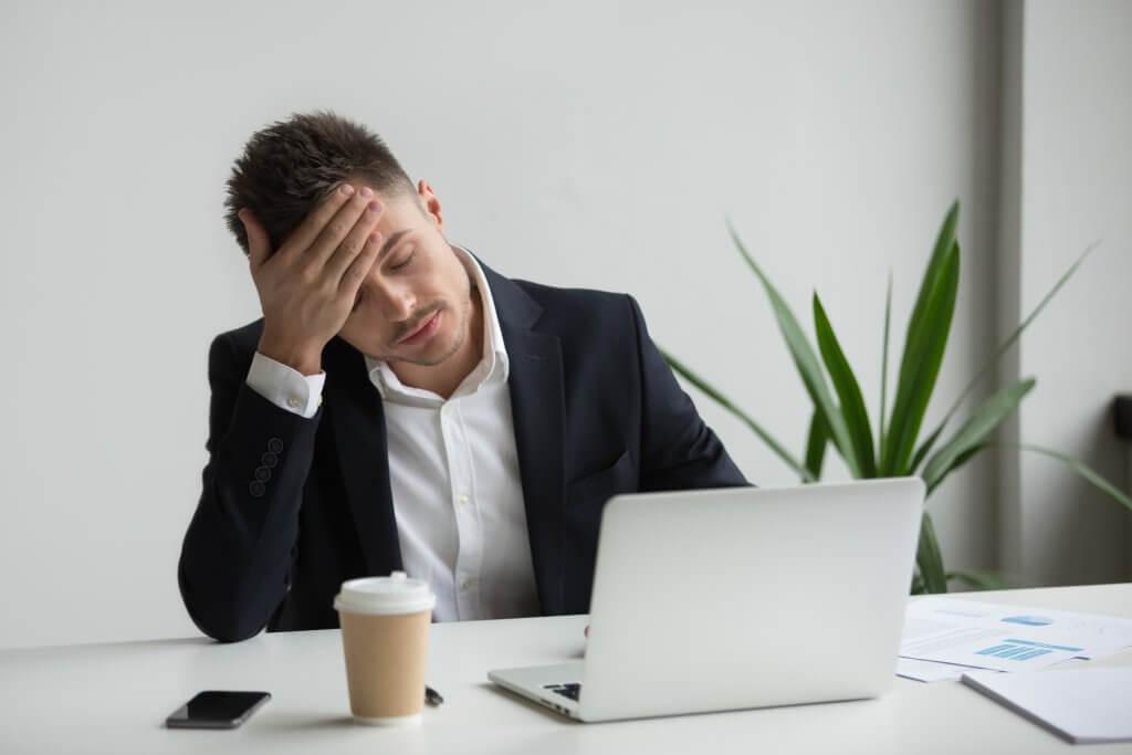 Frustrated-millennial-businessman-having-strong-headache-tired-from-laptop-work