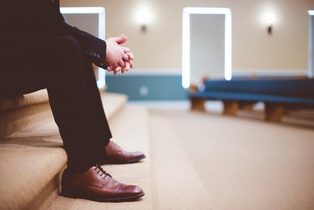man in black pants and pair of brown leather lace-up shoes sitting on brown carpeted stairs inside room waiting interview