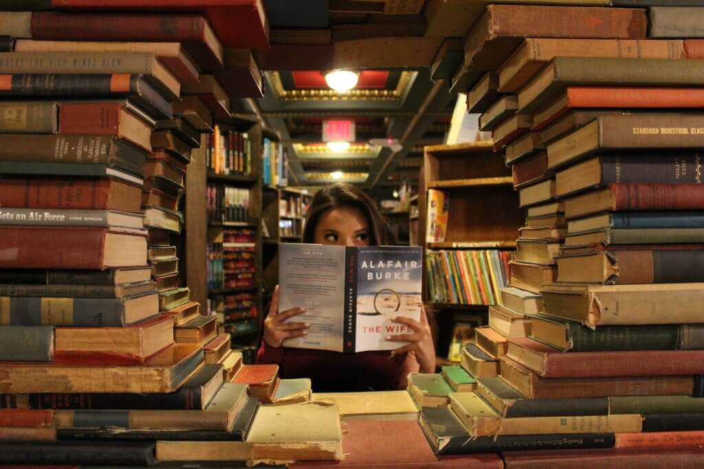 woman holding book around textbooks