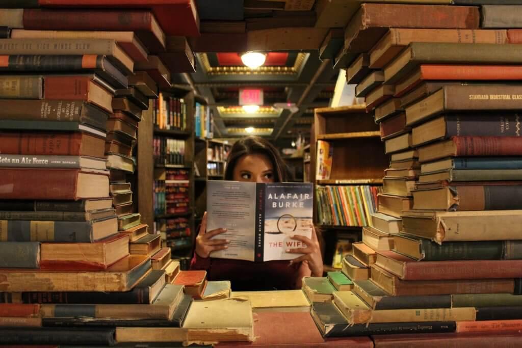 woman holding book around textbooks