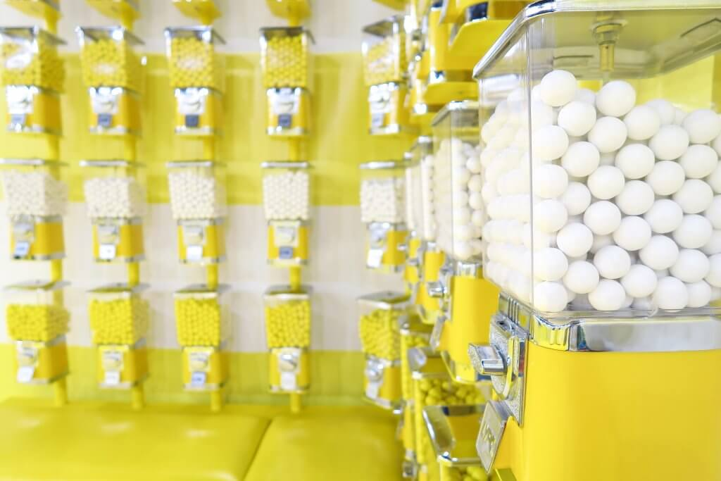 yellow candy dispenser filled with white candies, chewing gum is good for memory