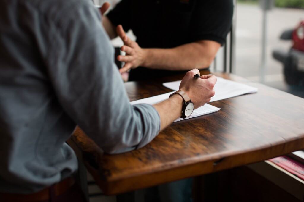 two person interview on paper on brown wooden table
